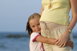 Double motherhood - pregnancy woman and her little daughter