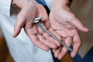 David Schneider MD holds medical device implant for orthopedic surgery, Photo by Ellen Jaskol.